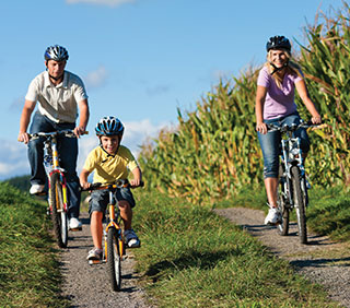 family-cycling-past-fields